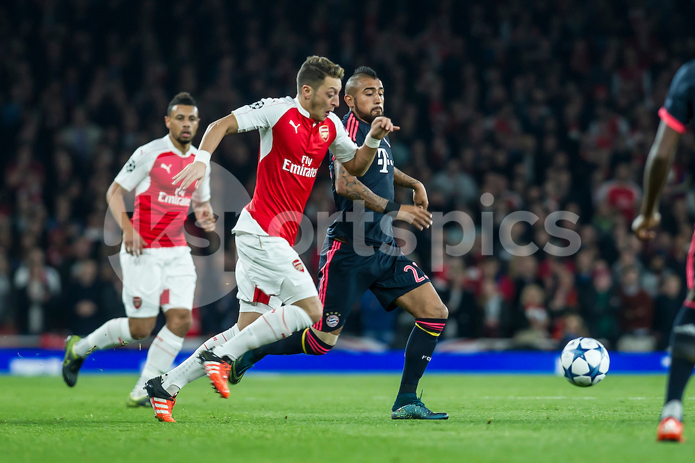 Mesut Özil of Arsenal and Arturo Vidal of Bayern Munich during the UEFA Champions League Group F match between Arsenal and Bayern Munich at the Emirates Stadium, London, England on 20 October 2015. Photo by Salvio Calabrese.