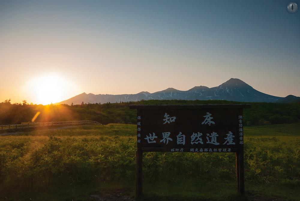 A sign stating 'Shiretoko: UNESCO World Heritage Site' taken from Furepe Falls in the Shiretoko Peninsula, Hokkaido with the sun rising behind its 7 iconic peaks.