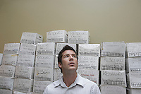 Business man standing in front of stack of filing boxes in storage room low angle view