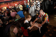 Ladies darts champion Anastasia Dobromyslova signs her autograph on a shirt for a male darts fan during England Open tournament