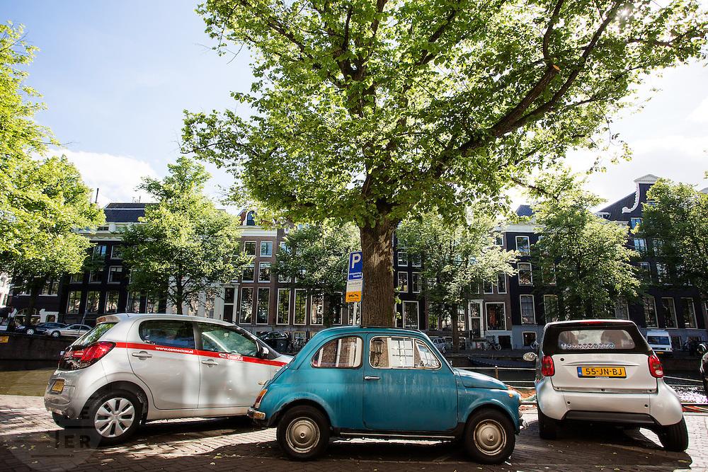In Amsterdam staan twee kleine auto's, een Smart en een oude Fiat 500, bij een deelauto geparkeerd aan de gracht.<br /> <br /> In Amsterdam a small Smart and an old Fiat 500 are parked next to a share car at the canals.