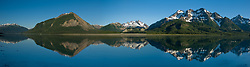 Mountain peaks on the south side of Adams Inlet are reflected in the  calm waters of Adams Inlet of Glacier Bay National Park and Preserve in southeast Alaska. Named peaks pictured are Tree Mountain (second mountain from left) and Mount Case (mountain at far right). The view is looking up the Adams Glacier valley (center). SPECIAL NOTE: This image is a panorama composite consisting of multiple overlapping images stitched together.