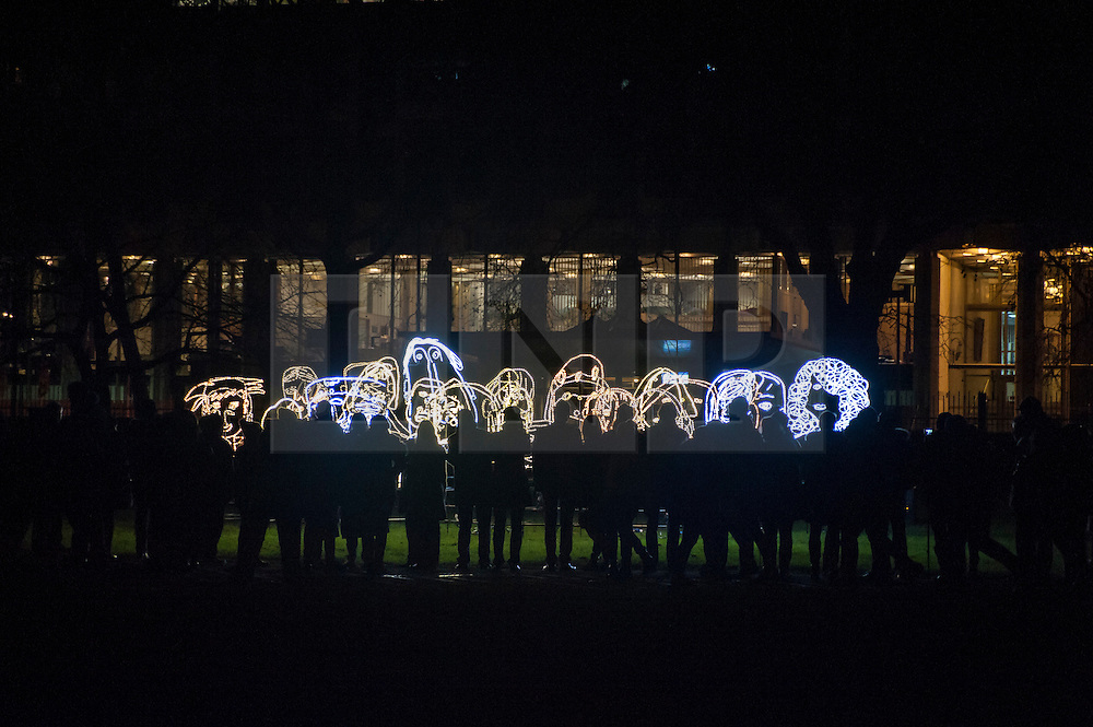 """© Licensed to London News Pictures. 15/01/2016. London, UK.  Visitors line up to see """"Brothers and Sisters"""" by Ron Haselden on display in Grosvenor Square.  The work forms part of Lumiere London, a major new light festival which is into the second of four evenings and featuring artists who work with light.  The event is produced by Artichoke and supported by the Mayor of London.  Photo credit : Stephen Chung/LNP"""
