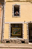 Man looking out of a window above an art gallery in Pont Aven
