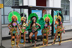 © Licensed to London News Pictures. 29/08/2016. London, UK. Carnival goers in costume waiting at a bus stop before taking part in day two of the Notting Hill carnival, the second largest street festival in the world after the Rio Carnival in Brazil, attracting over 1 million people to the streets of West London.  Photo credit: Ben Cawthra/LNP
