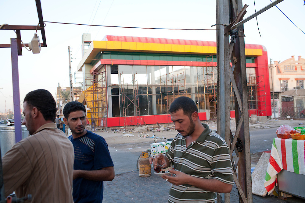 Men drink tea from a street vendor next to where a brand new Dell computer store is under construction on Friday, October 22, 2010 in Basrah, Iraq.