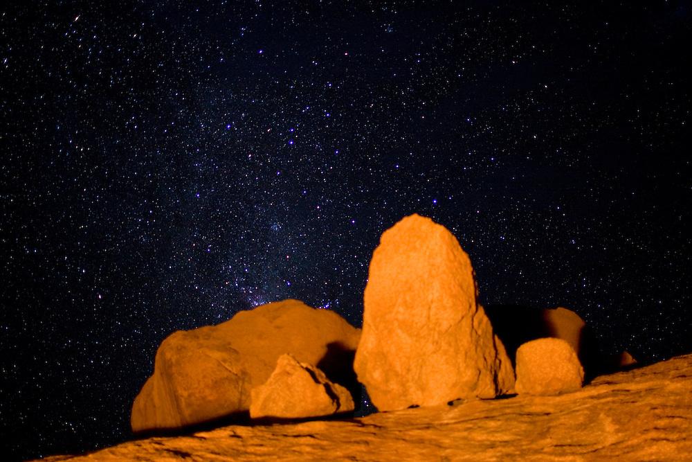 Africa, Namibia, Usakos, Orange light from campfire illuminates granite boulders near Spitzkoppe mountain below starry night sky in Namib Desert