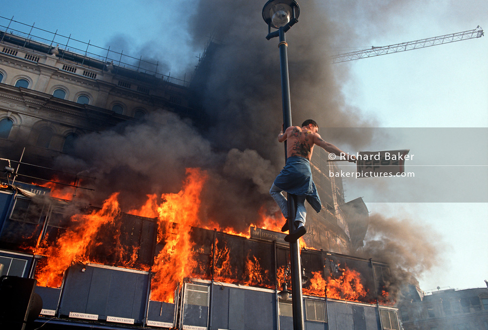 Several metres above the ground, a lone protester hangs on to a street light pole near London's Trafalgar Square at the height of the Poll Tax Riot on 31st March 1990, in Westminster, London, England. Angry crowds, demonstrating against Margaret Thatcher's local authority tax, stormed the Whitehall area and then London's West End, starting fires and overturning cars, looting stores up Charing Cross Road and St Martin's Lane. The anti-poll tax rally in central London erupted into the worst riots seen in the city for a century. Forty-five police officers were among the 113 people injured as well as 20 police horses. 340 people were arrested. (Photo by Richard Baker / In Pictures via Getty Images)