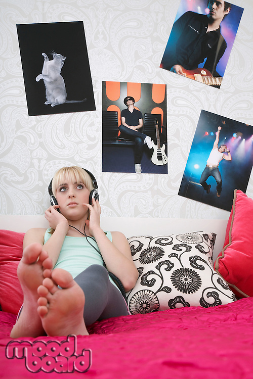 Teenage girl (16-17) sitting on bed listening to music