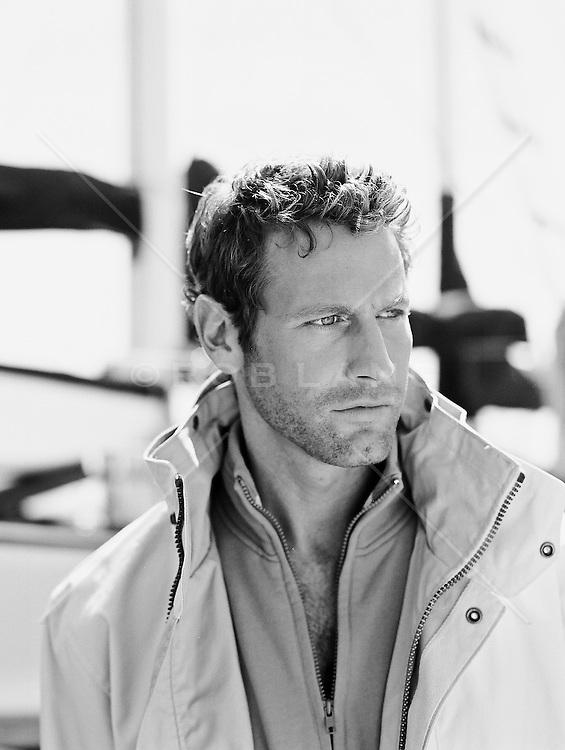 Good looking man in layered jacket at a marina