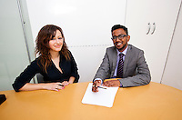 Multi-ethnic work colleagues signing paperwork on a table