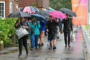 Spectator shelters from the rain under an umbrellas as they arrive ahead of the International Test Match 2019 match between England and Australia at Lord's Cricket Ground, St John's Wood, United Kingdom on 14 August 2019.