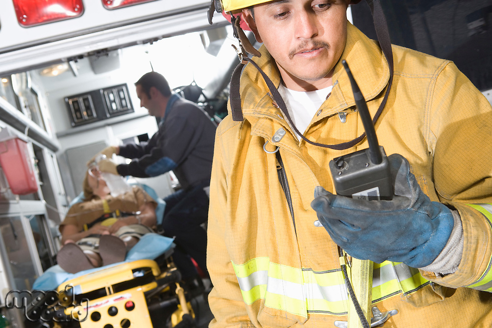 Firefighter using radio, paramedic tending victim