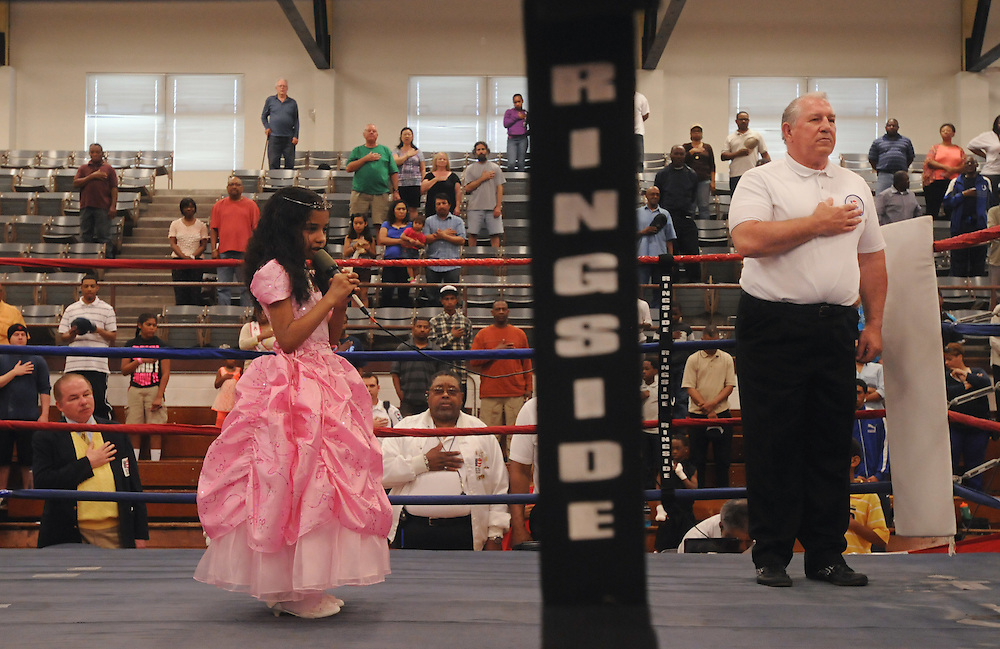 Shania Saeli, 7, sings the national anthem as boxing referee Bill Stankowski places his hand over his heart at the North Carolina Azalea Festival Boxing Tournament at Williston Middle School.Saturday, April 13, 2103. Photo by Mike Spencer
