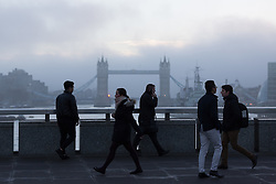 © Licensed to London News Pictures. 22/12/2016. LONDON, UK.  Commuters cross London Bridge during cold weather as fog begins to lift this morning. After a cold and foggy start to the day, London is now seeing bright and sunny weather today. Photo credit: Vickie Flores/LNP