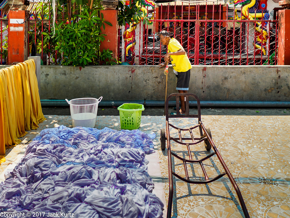 03 APRIL 2017 - BANGKOK, THAILAND: A man walks out of a slum area along the Chao Phraya River south of the Krung Thon Bridge in Bangkok. This is one of the first parts of the riverbank that is scheduled to be redeveloped. The communities along the river don't know what's going to happen when the redevelopment starts. The Chao Phraya promenade is development project of parks, walkways and recreational areas on the Chao Phraya River between Pin Klao and Phra Nang Klao Bridges. The 14 kilometer long promenade will cost approximately 14 billion Baht (407 million US Dollars). The project involves the forced eviction of more than 200 communities of people who live along the river, a dozen riverfront  temples, several schools, and privately-owned piers on both sides of the Chao Phraya River. Construction was  scheduled to start in early 2016 but had been pushed back to late 2017. There has been very little public input on the planned redevelopment.             PHOTO BY JACK KURTZ