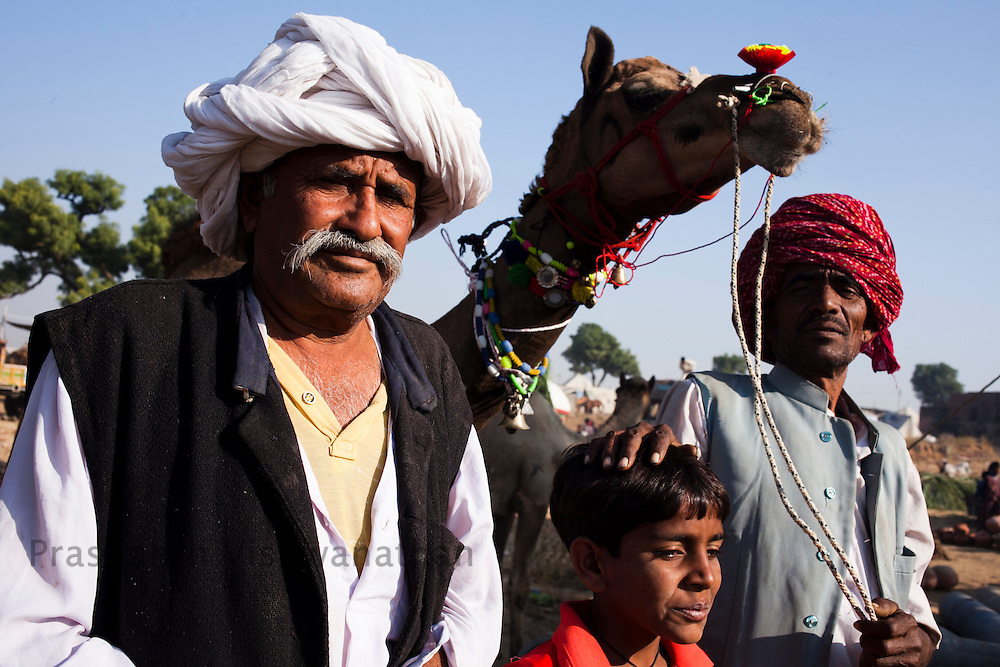 A family potrait joined in by their camel at the fair grounds in Pushkar, India, November 6, 2011.  Photographer: Prashanth Vishwanathan