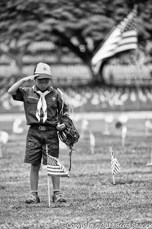 A salute by a Boy Scout after he placed a lei around the American flag adorning the headstone at Punchbowl. Images taken at the National Cemetery of the Pacific in preparation for Memorial Day 2011.