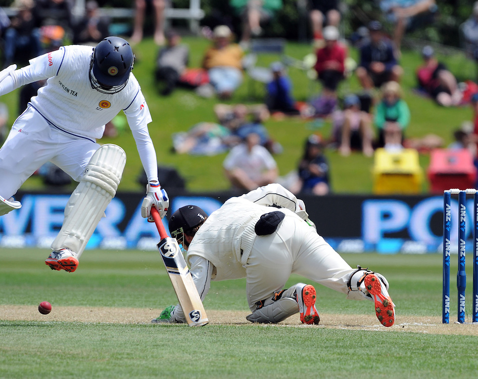 Sri Lanka's Dimuth Karunaratne leaps the ball as New Zealand's BJ Watling attempts to field on day two of the first International Cricket Test, University Cricket Oval, Dunedin, New Zealand, Friday, December 11, 2015. Credit:SNPA / Ross Setford
