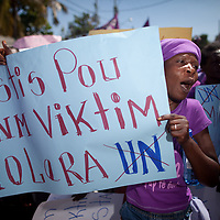 "A Women's Day protestor carries a sign that reads, ""Justice for women victims of cholera."" Two of the demands of the organizations supporting the march are withdrawal of UN troops and UN payment of reparations to cholera victims. (Photo by Ben Depp)"
