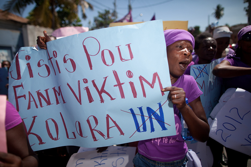 """A Women's Day protestor carries a sign that reads, """"Justice for women victims of cholera."""" Two of the demands of the organizations supporting the march are withdrawal of UN troops and UN payment of reparations to cholera victims. (Photo by Ben Depp)"""