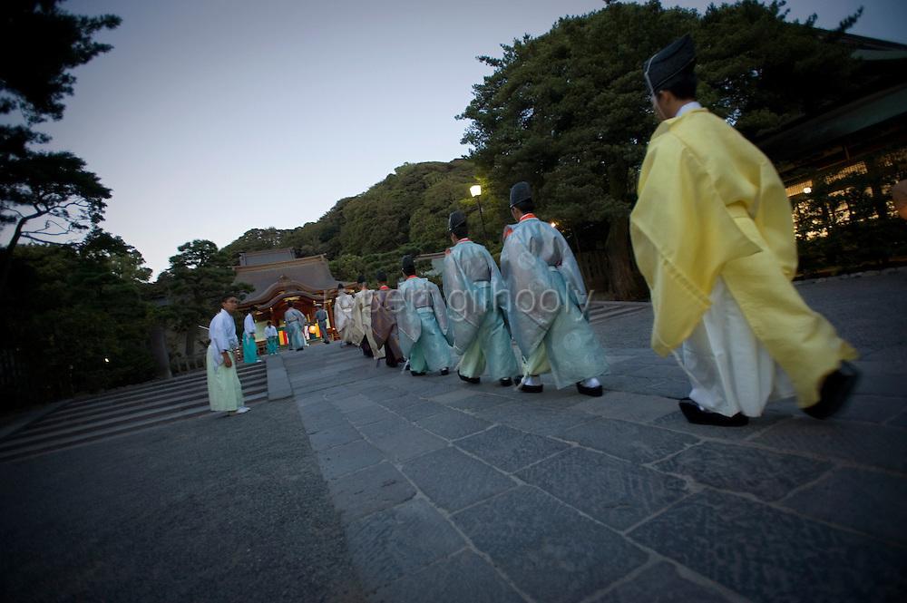 Priests make their way to a purification ritual in the grounds of Tsurugaoka Hachimangu shrine during he Yoimiyasai ritual that announces to the kami gods of the shrine the arrival of the upcoming Reitaisai grand festival  in Kamakura, Japan on  14 Sept. 2012.  Photographer: Robert Gilhooly