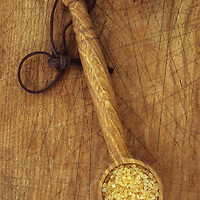 Small wooden scoop with long handle and leather hanging loop lying on chopping board and full of demerara sugar