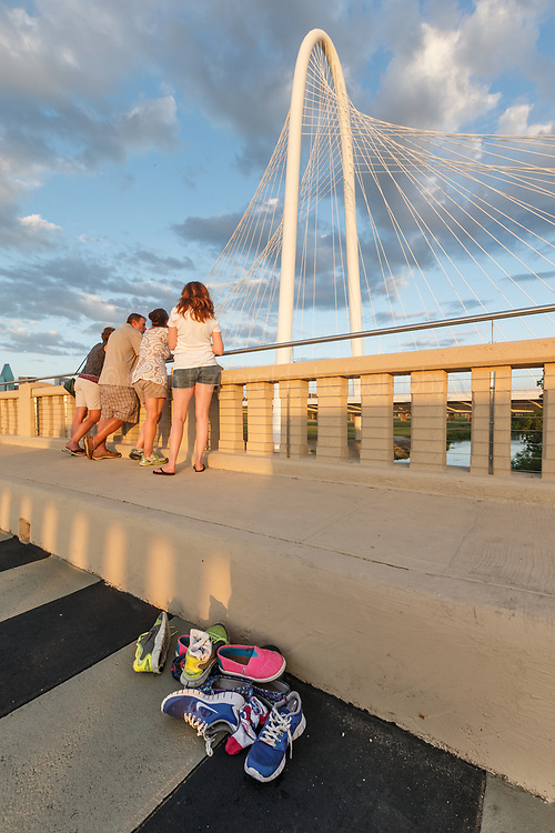 People and shoes on Continental Avenue Bridge with Margaret Hunt Hill Bridge in background, Trinity River, Dallas, Texas, USA.