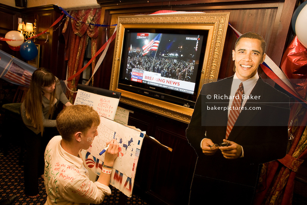 Democrat Party members keep up with latest results with life-size cardboard cut-out of Barack Obama during 2008 elections