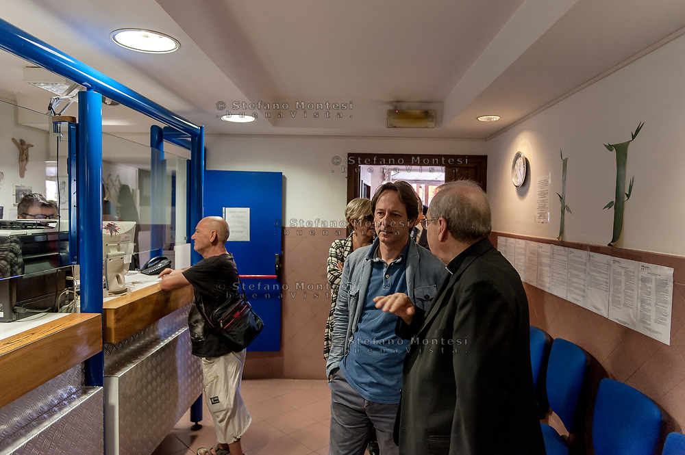 ROME, ITALY - AUGUST 15: The director of Caritas Rome, Msgr. Enrico Feroci and the Deputy Mayor Luca Bergamo during visits the Caritas canteen of Colle Oppio on the mid-August holiday on August 15, 2017 in Rome, Italy. Caritas canteen of Colle Oppio  provide about 500 meals a day for lunch.