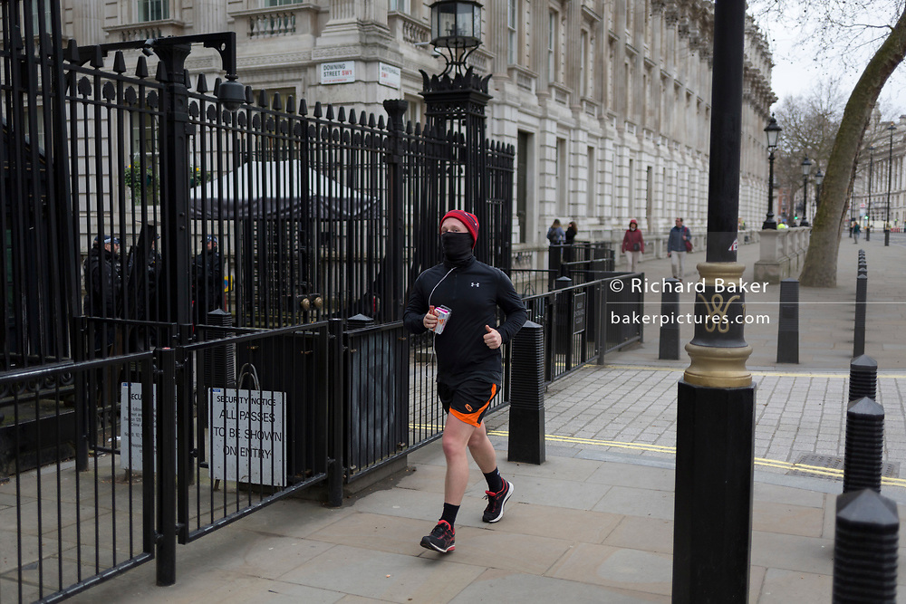 As the Coronavirus pandemic spreads across the UK, businesses and entertainment venues not already closed with the threat of job losses, struggle to stay open with growing rumours of a lockdown and travel restrictions around the capital. As Londoners start to work from home, a runner wearing a face mask passes the security gates of Downing Street, the official residence and office of Prime Minister Boris Johnson, on 19th March 2020, in London, England.