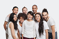 Portrait of young multi-ethnic friends smiling together against white background