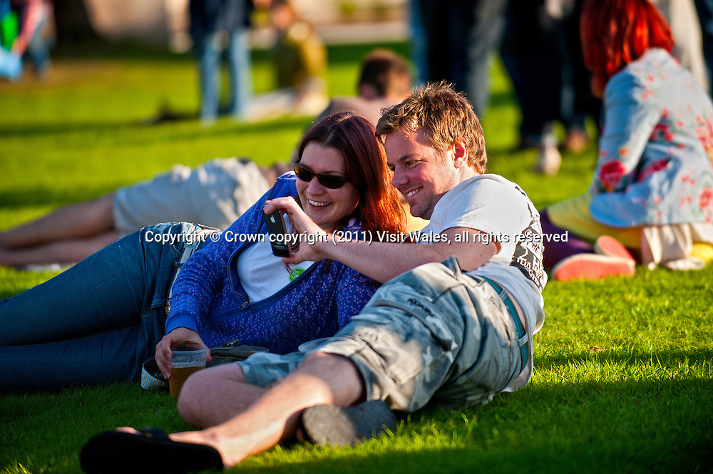 Couple lying outside in evening sun looking at iPhone<br /> Brecon Jazz <br /> 2011<br /> Brecon<br /> Powys<br /> South<br /> Music<br /> Arts<br /> Events