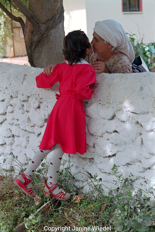 Young Turkish school girl greeting her grandmothern in small village in South Western Turkey.