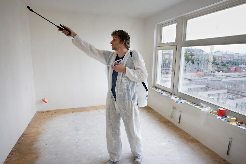 Nederland. Rotterdam, 26 juli 2007.<br /> Pim Bangert (spelling checken svp) behandelt de muur met primer om het verven te vergemakkelijken. Hij heeft in de wijk Spangen goedkoop een casco huis gekocht. Wijkverbetering. Repo Gerard Reijn.<br /> Foto Martijn Beekman <br /> NIET VOOR TROUW, AD, TELEGRAAF, NRC EN HET PAROOL
