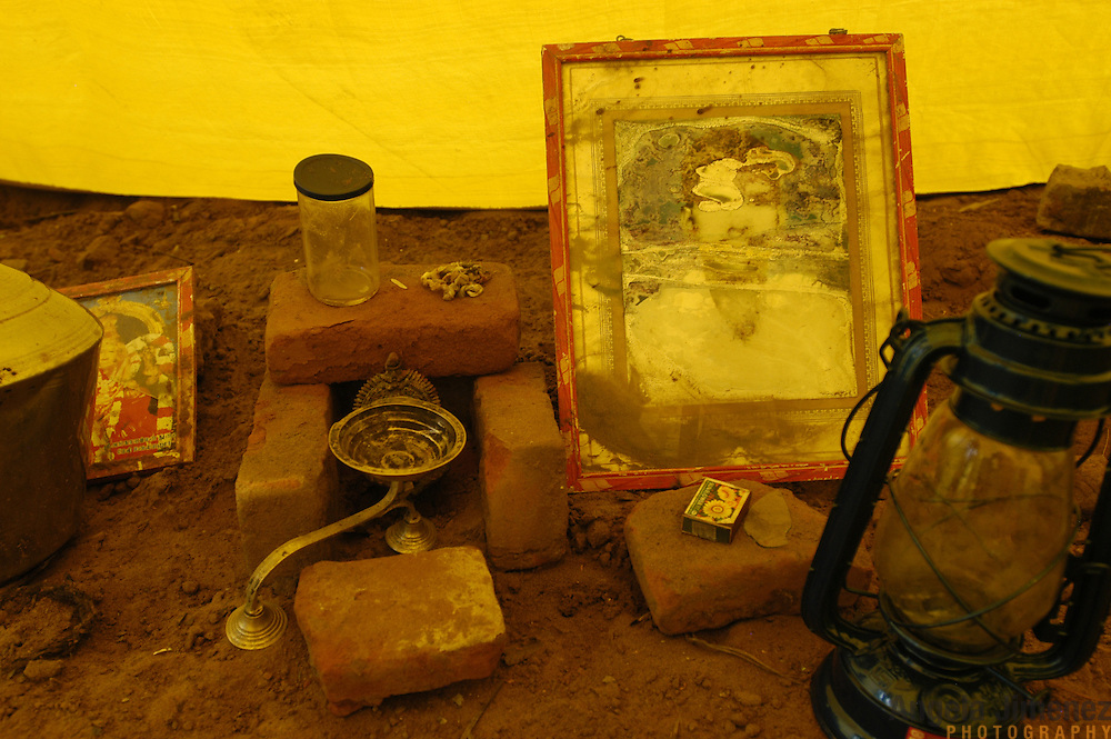 An altar set up by a young fisherman, Prakash M., 20, sits inside a government-issued relief tent on the spot where his family's home stood in the fishing village of Perumalpettai in Tami Nadu, India, on January 21, 2005. His home was washed away and his mother was killed by the Indian Ocean Tsunami on December 26, 2004; Prakash salvaged this water-damaged photo of his father, who was previously deceased, from the wreckage. Generated by an earthquake on the ocean floor, the tsunami devastated the fishing industry along the southeastern coast of India.