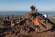 """Walkers enjoy summer evening sunshine on the summit of Arthur's Seat in Holyrood Park, overlooking the city of Edinburgh and the Firth of Fourth estuary, on 26th June 2019, in Edinburgh, Scotland. Arthur's Seat is an extinct volcano which is considered the main peak of the group of hills in Edinburgh, Scotland, which form most of Holyrood Park, described by Robert Louis Stevenson as """"a hill for magnitude, a mountain in virtue of its bold design"""". The hill rises above the city to a height of 250.5 m (822 ft), providing excellent panoramic views of the city and beyond."""