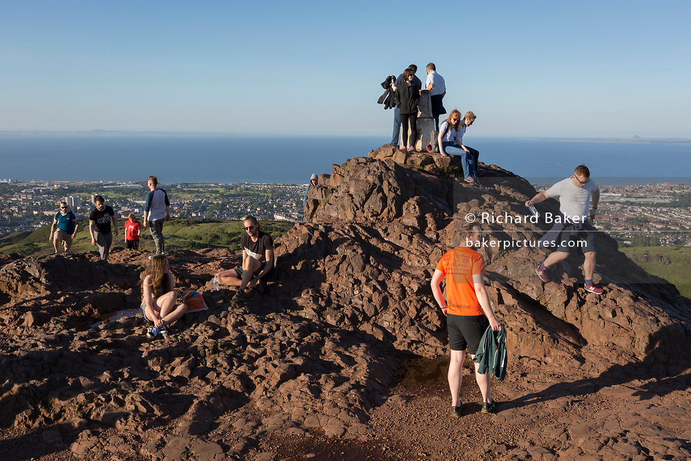 "Walkers enjoy summer evening sunshine on the summit of Arthur's Seat in Holyrood Park, overlooking the city of Edinburgh and the Firth of Fourth estuary, on 26th June 2019, in Edinburgh, Scotland. Arthur's Seat is an extinct volcano which is considered the main peak of the group of hills in Edinburgh, Scotland, which form most of Holyrood Park, described by Robert Louis Stevenson as ""a hill for magnitude, a mountain in virtue of its bold design"". The hill rises above the city to a height of 250.5 m (822 ft), providing excellent panoramic views of the city and beyond."