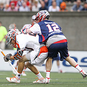 Drew Snider #23 of the Denver Outlaws avoids Martin Bowes #12 of the Boston Cannons during the game at Harvard Stadium on May 10, 2014 in Boston, Massachusetts. (Photo by Elan Kawesch)