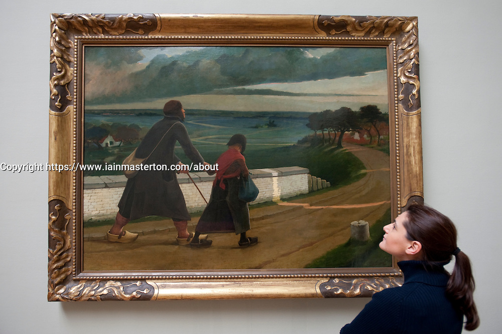 Visitor looking at painting Blind Man by Eugene Laermans at Royal Museum for Fine Arts in Antwerp Belgium