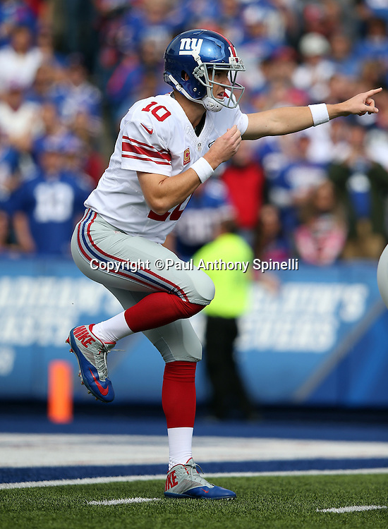 New York Giants quarterback Eli Manning (10) points at the defense as he kicks up his foot in a shotgun formation during the 2015 NFL week 4 regular season football game against the Buffalo Bills on Sunday, Oct. 4, 2015 in Orchard Park, N.Y. The Giants won the game 24-10. (©Paul Anthony Spinelli)