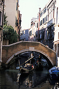 Gondolier steering gondola under an arched foot bridge, Venice, Italy..Subject photograph(s) are copyright Edward McCain. All rights are reserved except those specifically granted by Edward McCain in writing prior to publication...McCain Photography.211 S 4th Avenue.Tucson, AZ 85701-2103.(520) 623-1998.mobile: (520) 990-0999.fax: (520) 623-1190.http://www.mccainphoto.com.edward@mccainphoto.com..