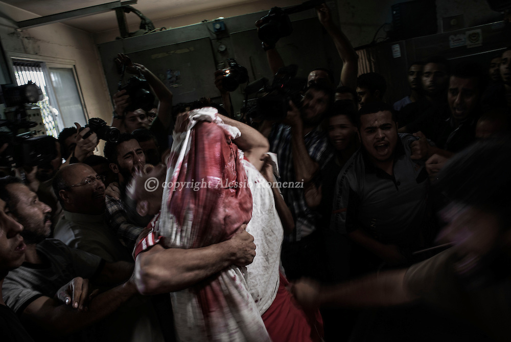 Gaza Strip, Gaza City: A Palestinian man cries as he holds the dead body of his young brother shortly after he got killed by an Israeli naval bombardment in the port of Gaza City in the morgue of the Shifa hospital in Gaza, 16 July 2014. ALESSIO ROMENZI