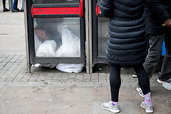 © Licensed to London News Pictures . 06/04/2017 . Manchester , UK . A man lies curled up on the floor of a telephone box after consuming a rolled cigarette believed to contain spice . An epidemic of abuse of the drug spice by some of Manchester's homeless population , in plain sight , is causing users to experience psychosis and a zombie-like state and is daily being witnessed in the Piccadilly Gardens area of Manchester , drawing large resource from paramedic services in the city centre . Photo credit : Joel Goodman/LNP