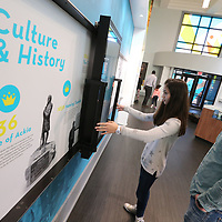 Averi Coleman, 11, and her father, Allen, use an interactive monitor to learn the history of this area along a timeline at the Convention and Vistors Bureau Thursday in Tupelo.