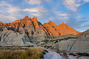 Golden sunset illuminates layers of ancient sediments on the Loop Road near the Interior Entrance of Badlands National Park, South Dakota, USA. This park has the largest undisturbed mixed grass prairie in the United States.