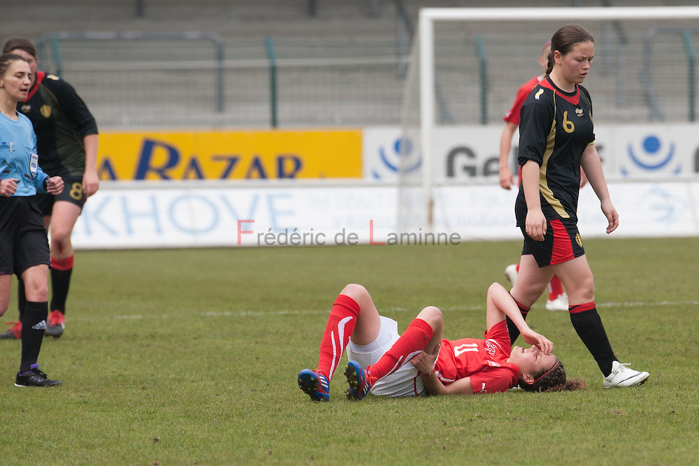 21120413 - HARELBEKE, BELGIUM : Switzerland's  Sabrina Ribeaud (11)  is on the ground as Belgium's  Valentine Hannecart (6)  walks nearby during the Second qualifying round of U17 Women Championship between Switzerland and Belgium on Friday April 13th, 2012 in Harelbeke, Belgium.