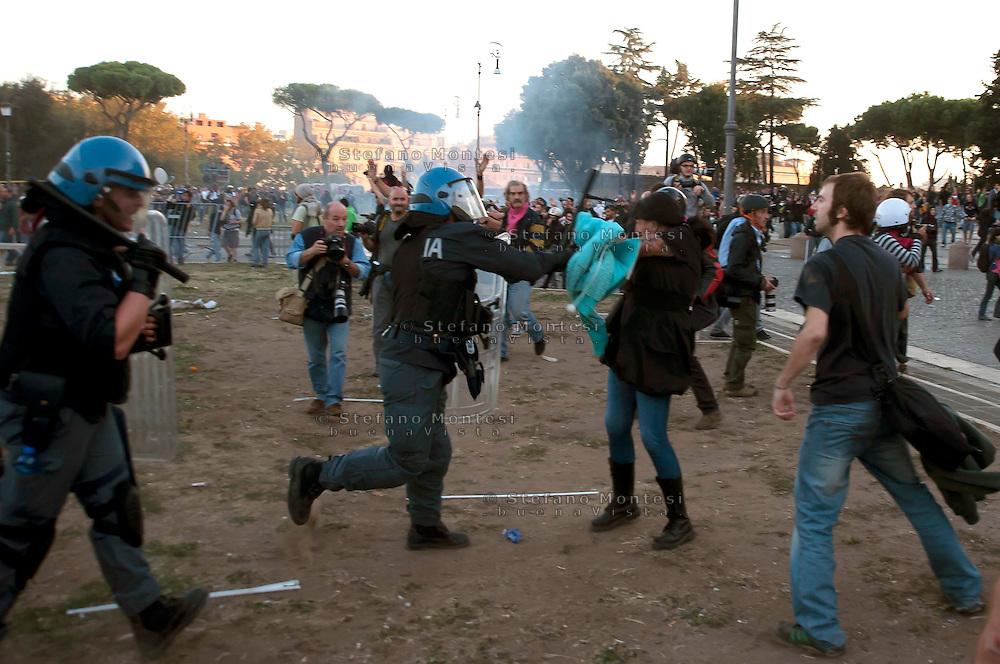 Roma  15 Ottobre 2011.Manifestazione contro la crisi e l'austerità.Scontri tra manifestanti e forze dell'ordine.La polizia carica i manifestanti non coninvolti negli scontri sul piazzale antistante la Basilica di San Giovanni, una ragazza viene colpita con il manganello.