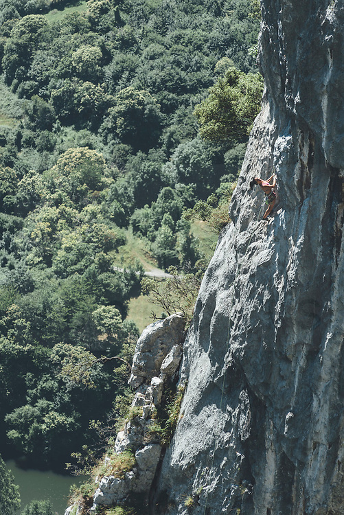 Marture woman climber climbing in a limestone cliff close to a dam Mamut climbing athlete Bobbi Bensman enjoying a climbing trip at Roca Verde, Asturias, Spain