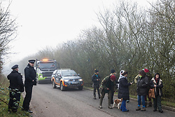 Denham, UK. 6 February, 2020. Police officers monitor environmental activists from Save the Colne Valley, Stop HS2 and Extinction Rebellion walking at a snail's pace along a road so as to block for several hours a security vehicle and truck delivering fencing and other supplies to be used for works associated with the HS2 high-speed rail link close to the river Colne at Denham Ford.